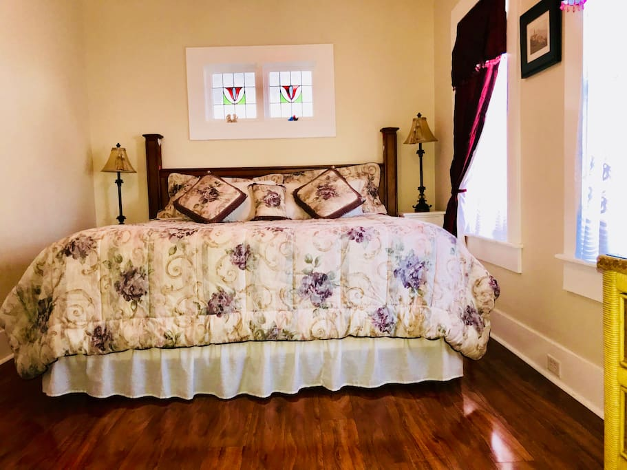 Super comfortable king size bed! Notice original stained glass window over the bed!