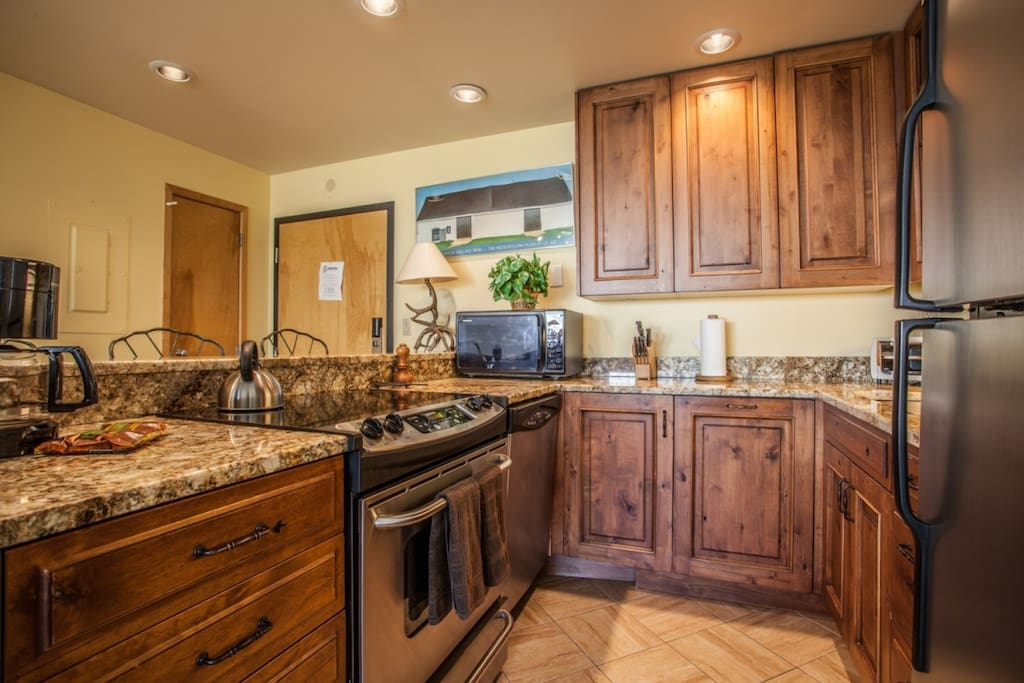 Fully equipped kitchen with granite counter tops, electric glass cook top and stainless appliances.