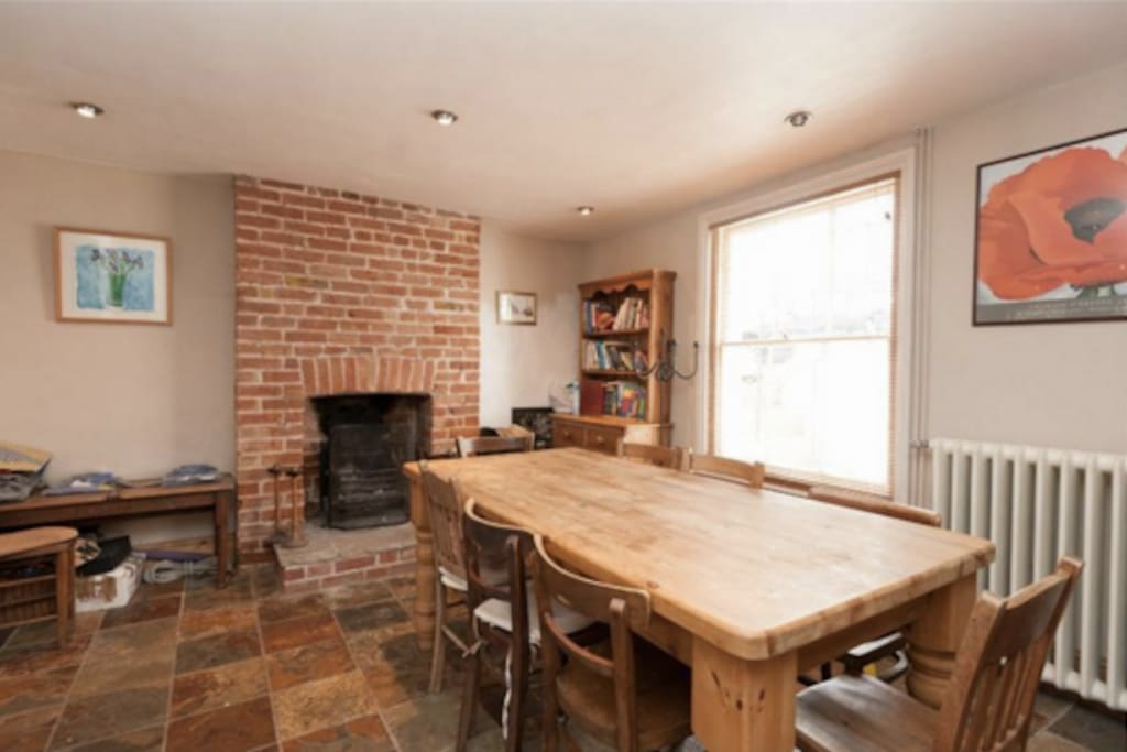 Large dining table and open fireplace. Open plan to cooking area, separated with a breakfast bar with 2 comfy stools.