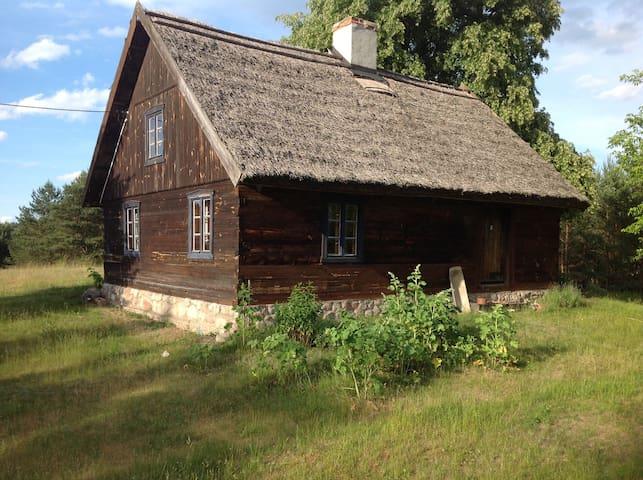 Dom pod strzechą na skraju lasu