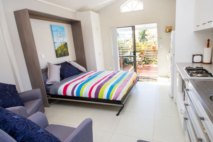 With the comfortable Tilt-Away Queen size Bed extended and ready to use, why not relax and watch that favourite TV show, or continue reading your favourite book!  Your own private entrance and the lovely practical covered deck are in the background.