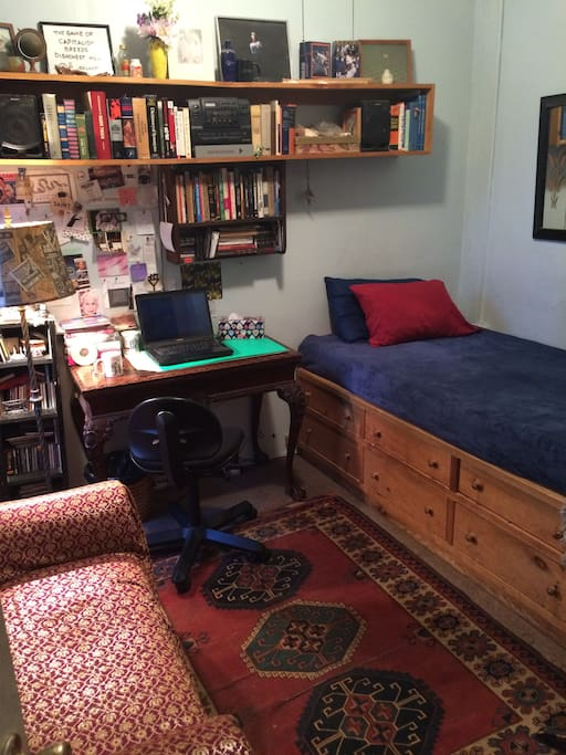 Guest room has a large desk for working -- and a settee for relaxing