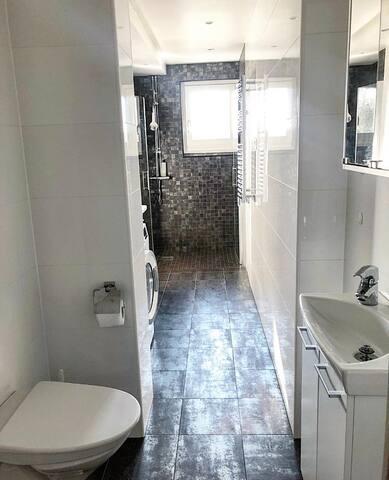 Stort badrum med handfat, wc och dusch samt tvättdel med tvättmaskin. Grått granitgolv och vitt kakel.