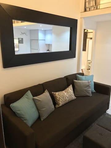 Vista al área de sala. En ella contamos con smart TV  y un sofá cama Queen size en el que puede acomodar fácilmente a dos personas.
