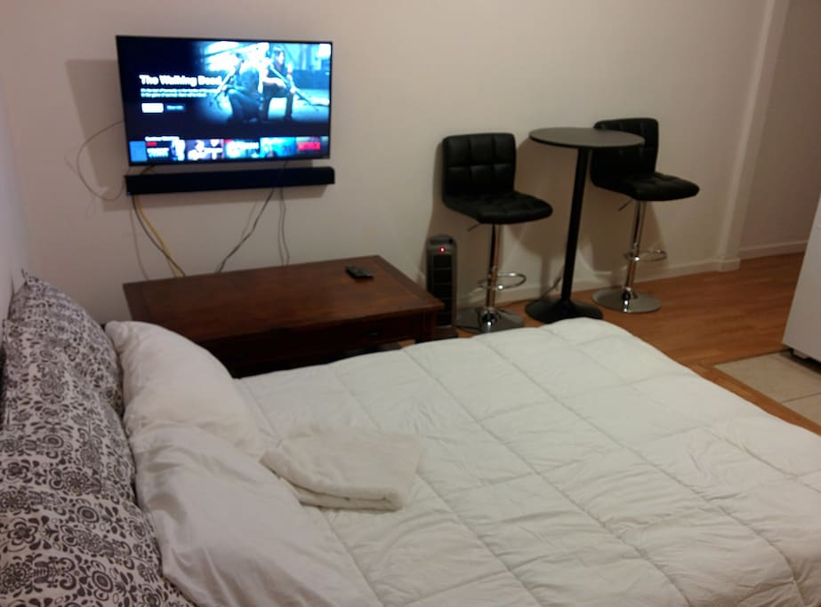 View of the bed, smart TV, coffee and kitchen table from the front door