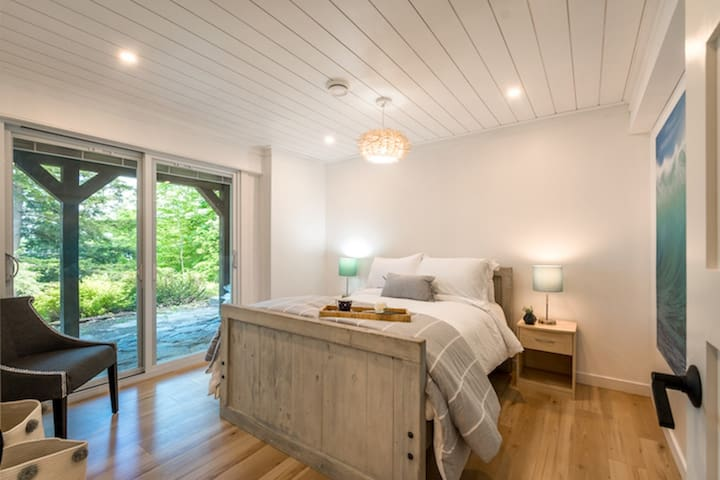 Downstairs bedroom with double bed and sliding patio door. Room has a lake view