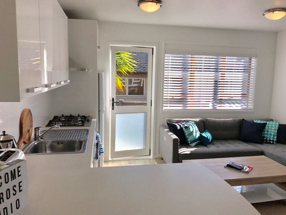 Living area with kitchenette and breakfast bar. Door to small out door deck area