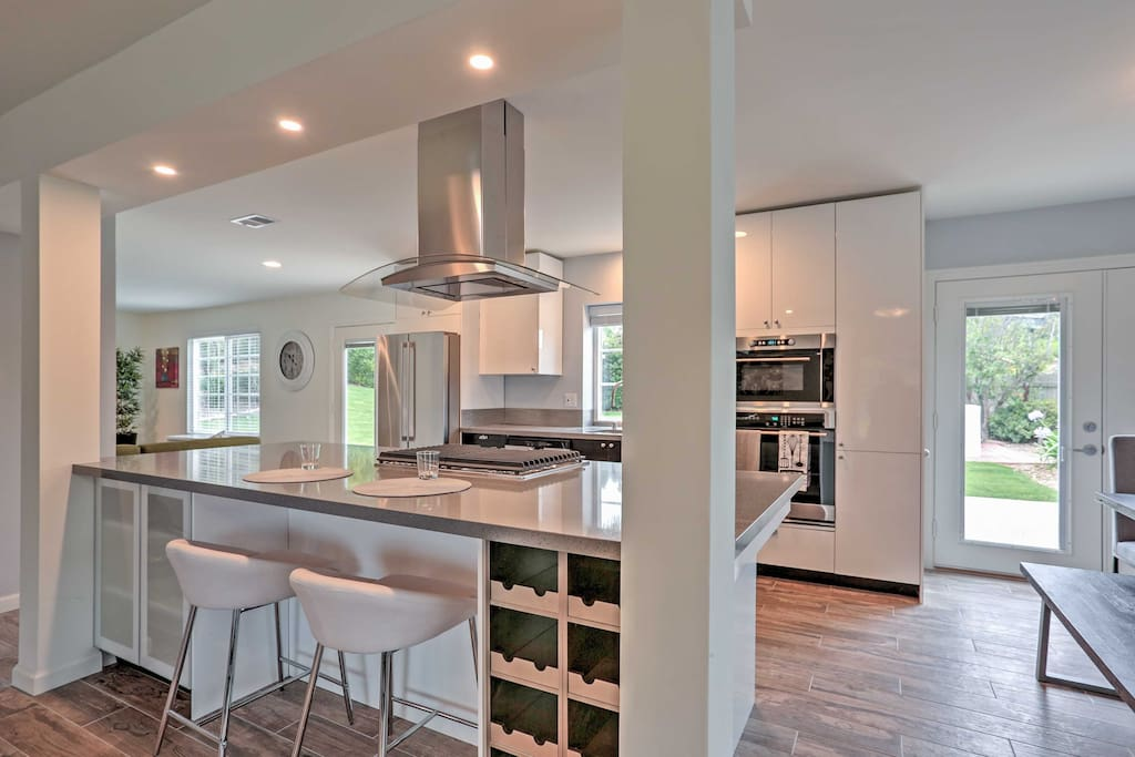 The fully equipped kitchen boasts stainless steel appliances and stovetop island