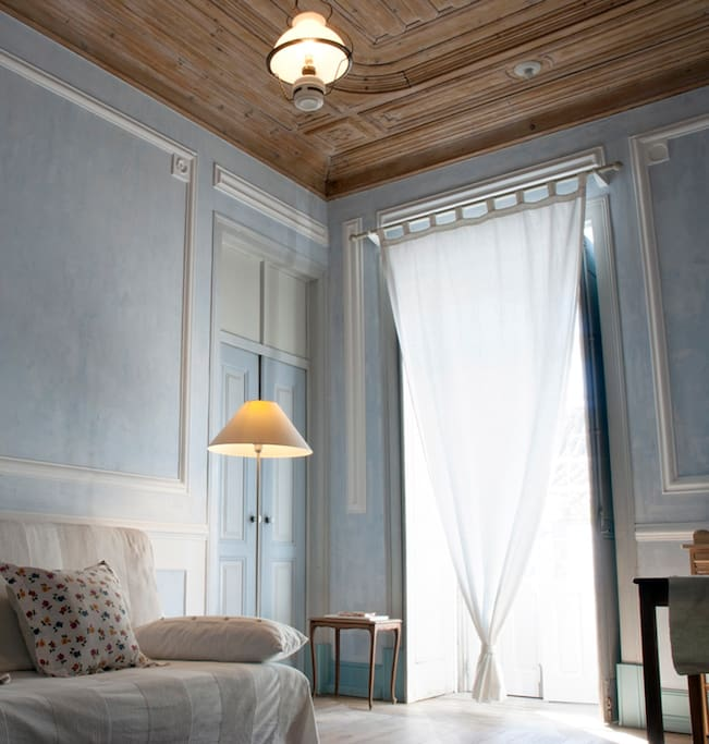 living room: french window; blue stucco render, wooden ceiling and floor.