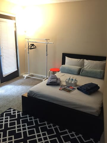 Guest Room. [A full size bed, bed side table, desk, chair, and a hanger rack]
