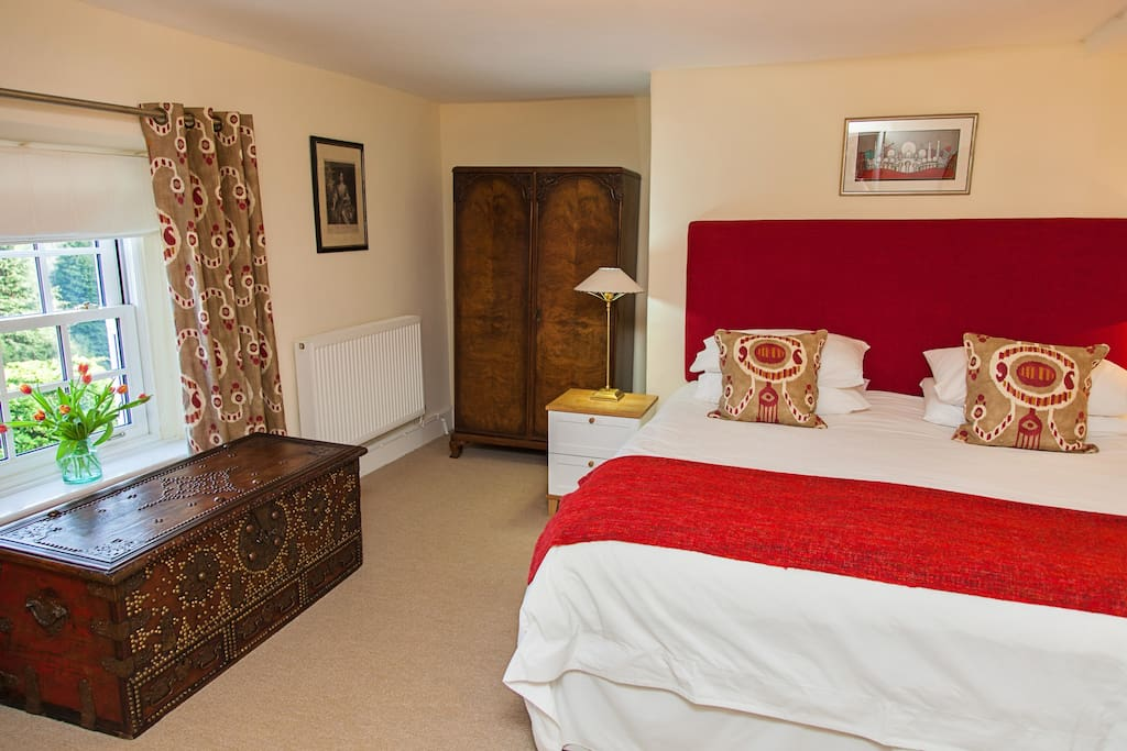 Master bedroom with Super king size bed.  En-suite includes large shower and tub. Views over the gardens and valley.