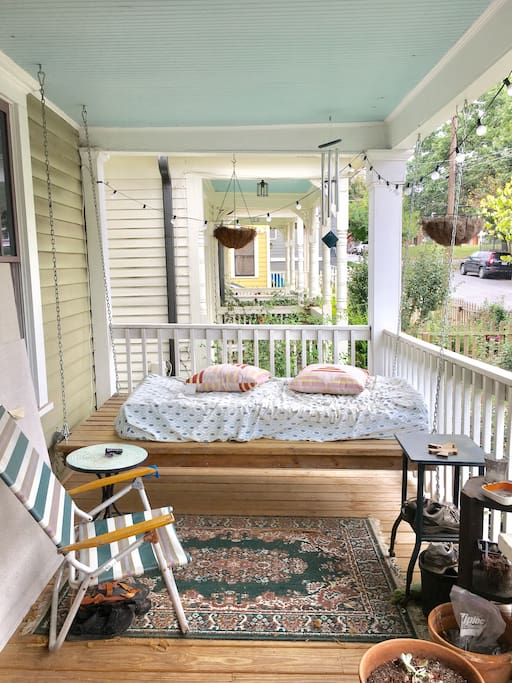 Our big front porch offer multiple seating options including the hanging bed!
