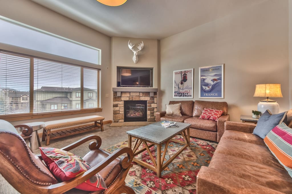 """Spacious Living Room with Comfortable Leather Furnishings, 60"""" LG Smart TV, Blu-ray DVD, and Gas Fireplace"""