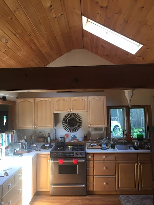 A fully-equipped kitchen with propane range, modern refrigerator, dishwasher, microwave & toaster, skylight