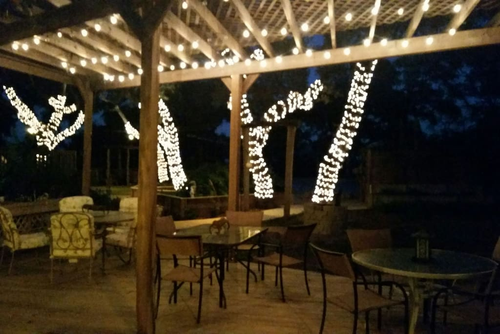 Patio deck with outdoor seating, with romantic lighting.
