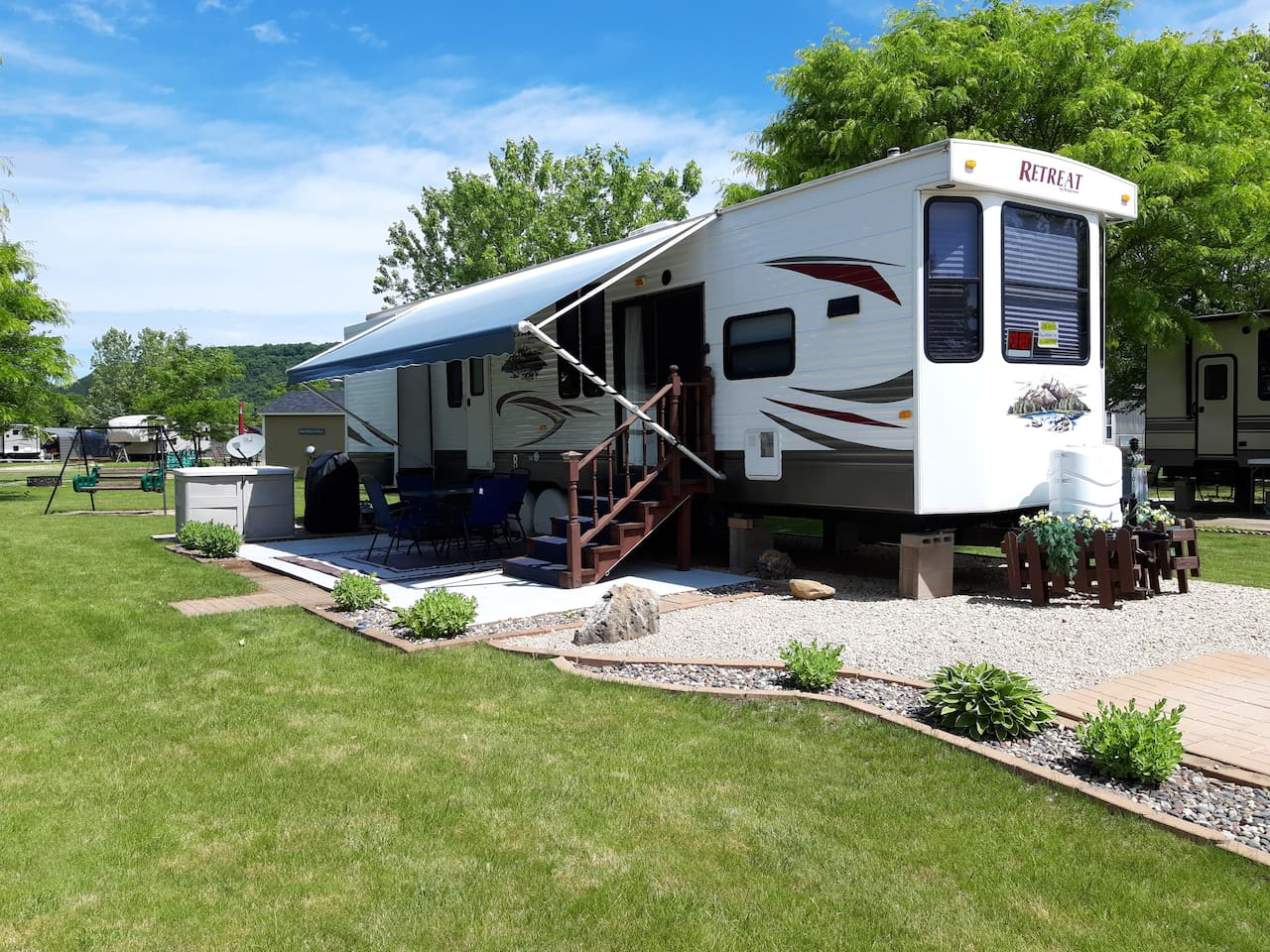 Open concept living area with a  separate bedroom and bathroom. Patio set under the awning, gas grill, fire pit in the yard, little porch with 2 chairs on the shed  and a yard swing.  Just bring clothes, food & firewood.