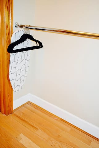Walk in  closet with hangers, table and Iron.