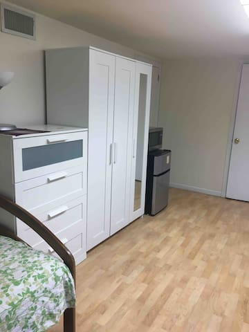 Several storage areas including chest of drawers, cabinet, and wardrobe with rail, shelves, and full-length mirror. Fridge & microwave.