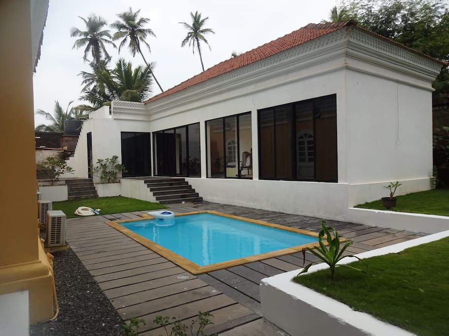 swimming pool nestled between the villa and the cottage