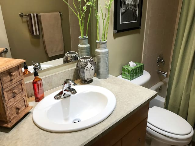 Clean private bathroom with plenty of natural light, tub, and shower.