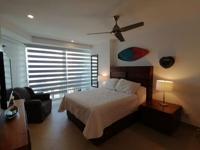 Queen Size Bed, ceiling fan, AC and TV, there´s a large window with lots of natural light