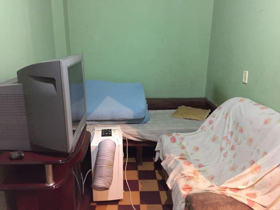 Espaço compartilhado com um sofá, e uma cama de solteiro, mais um colchão. tem ventilador na parede.