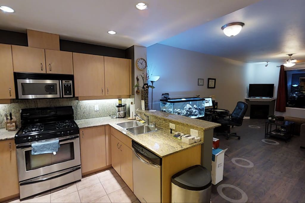 Kitchen with microwave, oven, refrigerator, stove, dishwasher, coffee machine, wine rack, and juicer.