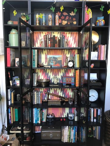 """Shelf-o-amusement! Peruse an antique book, play Scrabble or do a Sudoku, research a hike to do next week--you'll find plenty to do in this """"cozy den of personal treasures""""."""