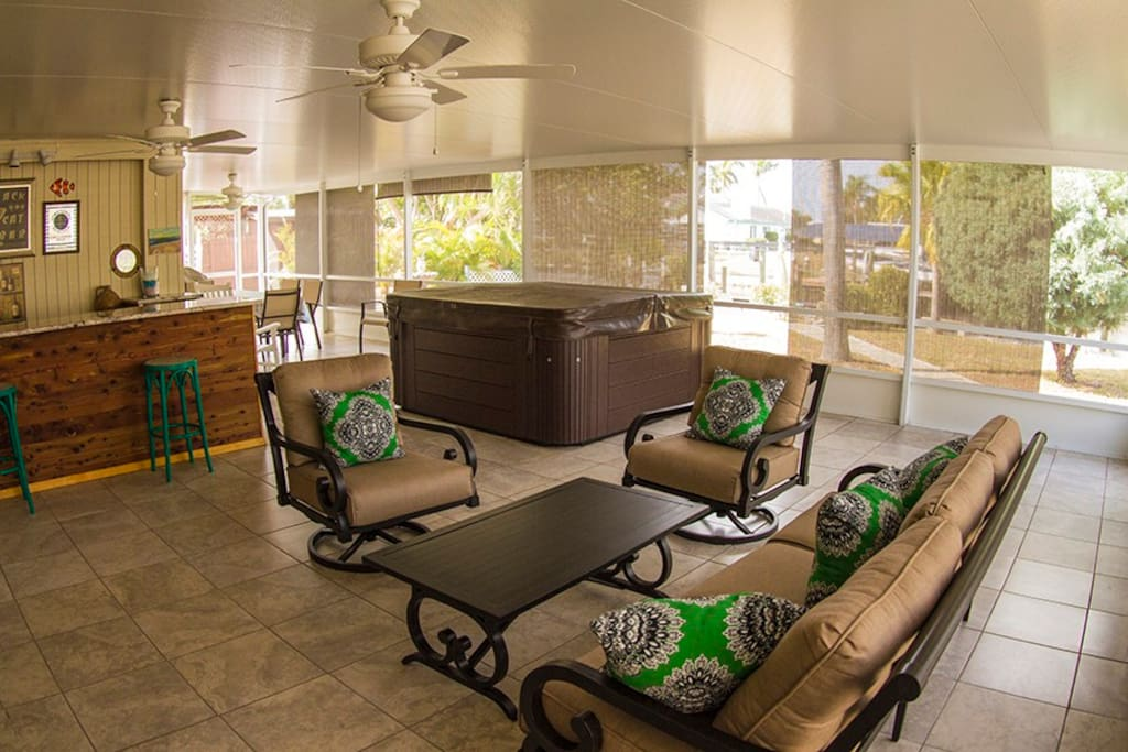 Lanai with hot tub, conversation area with TV, bar, dining area, and gas BBQ
