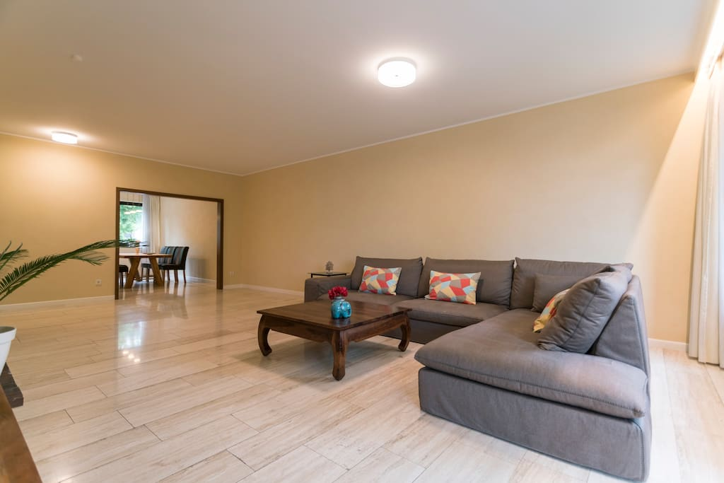 """Spacious living room with 55"""" TV and music system (DAB, Airplay etc.). Access to the large balcony (garden view)"""