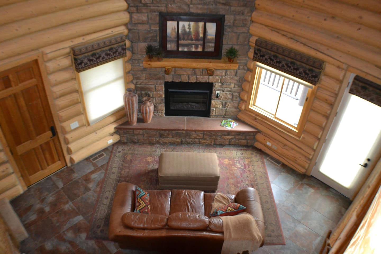 Living area with couch and ottoman.  The electric fire place will keep most of the house warm and cozy.