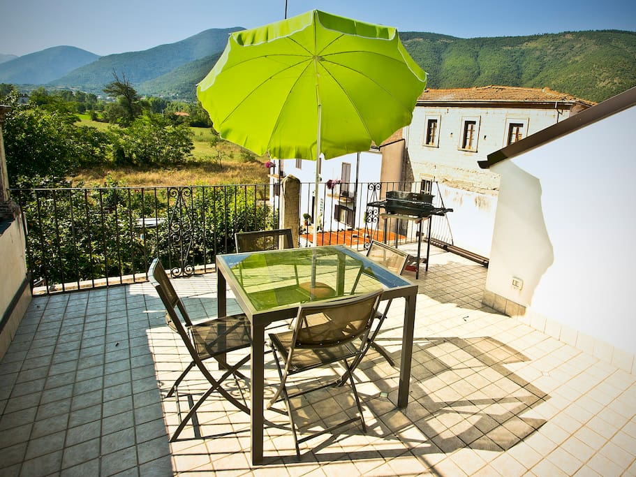 View off of the terrace, with barbecue, table and parasol.