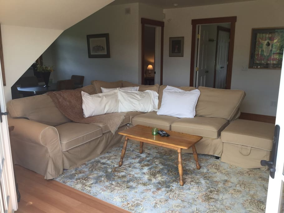 """Living Room (two BR doors in back of photo, dining table on left) with a much-too comfortable sofa (easy for two to """"couch potato"""" lol) with ottoman"""