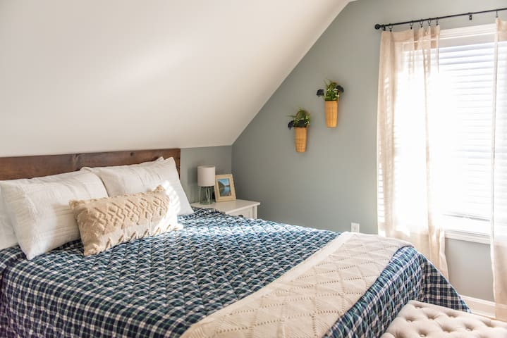 Our 2nd guest bedroom is upstairs, features a queen-size bed with a firm mattress, 2 nightstands, a padded bench for your suitcase, a small desk & stool for getting ready, and a small closet.  The decor is inspired by Acadia National Park.