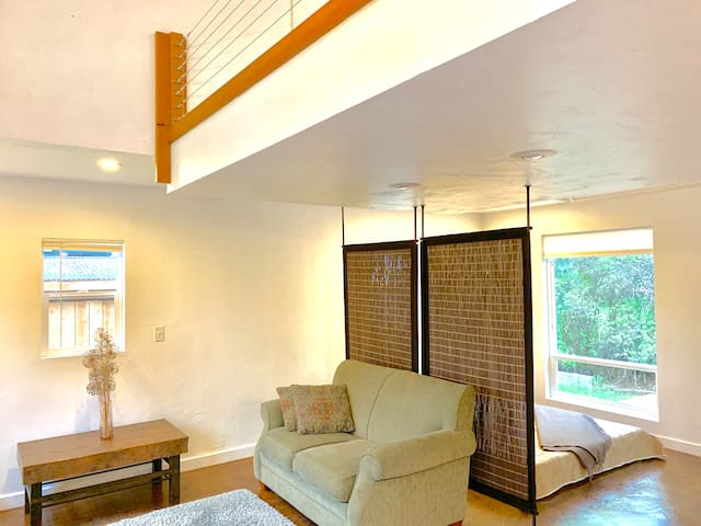 Living space and south-facing windows. Sleeping area and queen bed to the right of the privacy screen.
