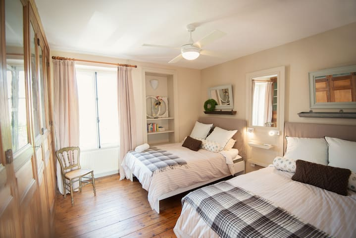 Third bedroom has two double beds and is surrounded by 18th-century shelves