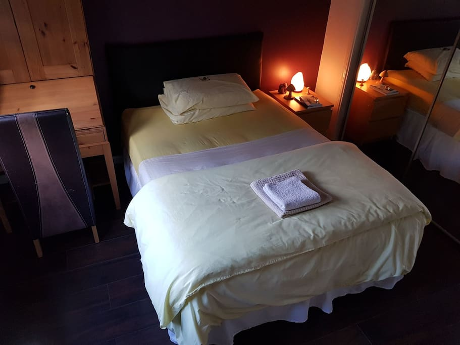 Double bed with complimentary tumble stone crystal and description card on pillow (1 crystal per guest)