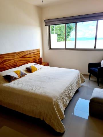 Vista recámara dos con cama KS que comparte baño con recámara tres equipada con dos camas matrimoniales.