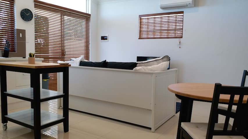 A bright and airy living room comes  complete with a sofa bed, a Smart TV, a dining table and a kitchen work table.  There is an aircon/heater which you can use anytime.