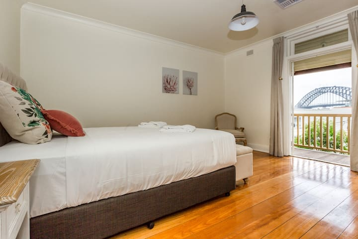 A master bedroom features a queen bed dressed in hotel-quality linen and access to a furnished outdoor balcony that boasts stunning, gun barrel views of the Harbour Bridge