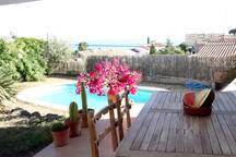 Amplio jardín con piscina con zona para comer y gran solarium.