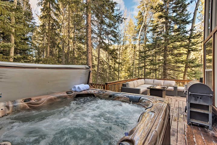 The deck features an outdoor fire pit, a gas/charcoal grill, and hot tub.