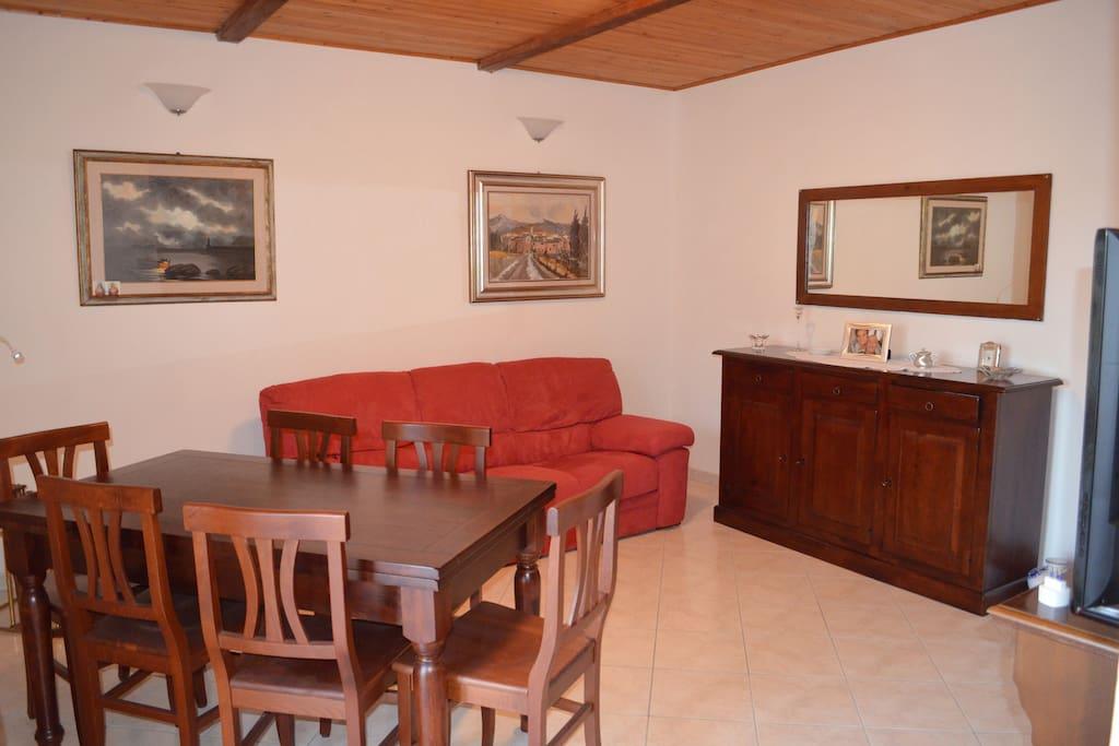 salotto con divano, ampio tavolo e televisore 42 pollici