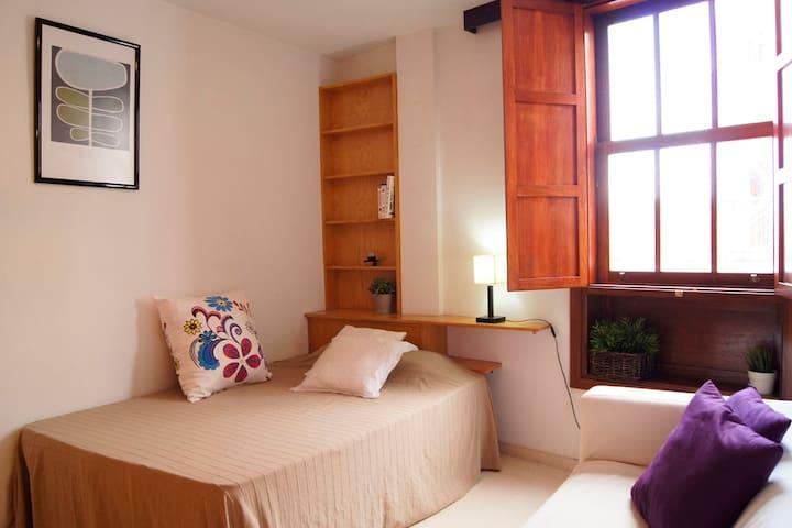 Dormitorio matrimonio con armario empotrado un pequeño sofá. Ventana hacia la terraza.