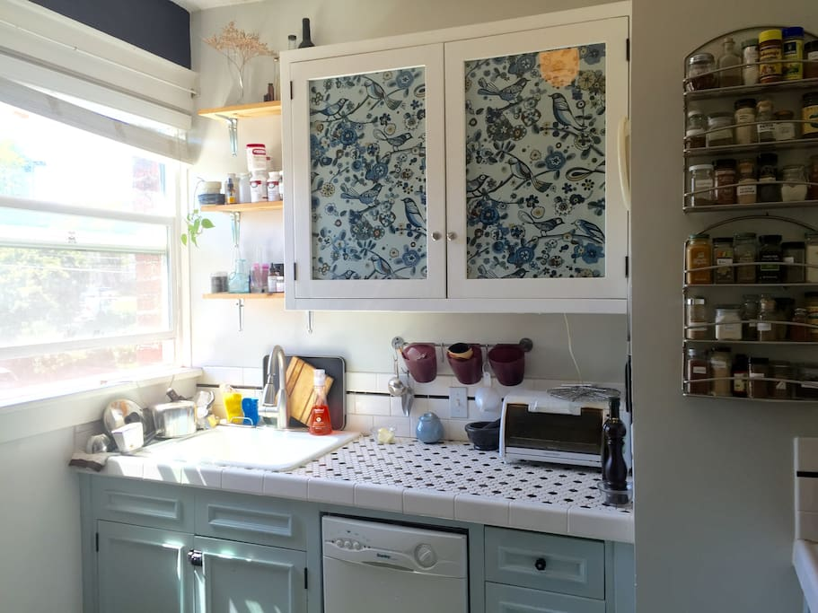 Bright kitchen with farmhouse sink, gas stove, dishwasher, and full size refrigerator.