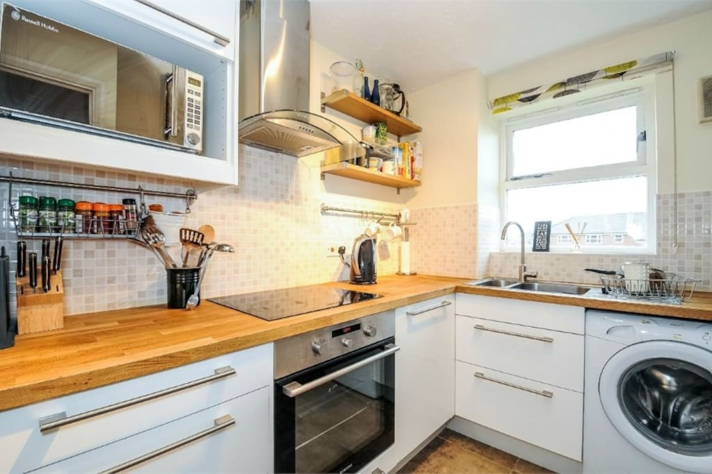 Modern kitchen with washing machine and dishwasher and cooking equipment