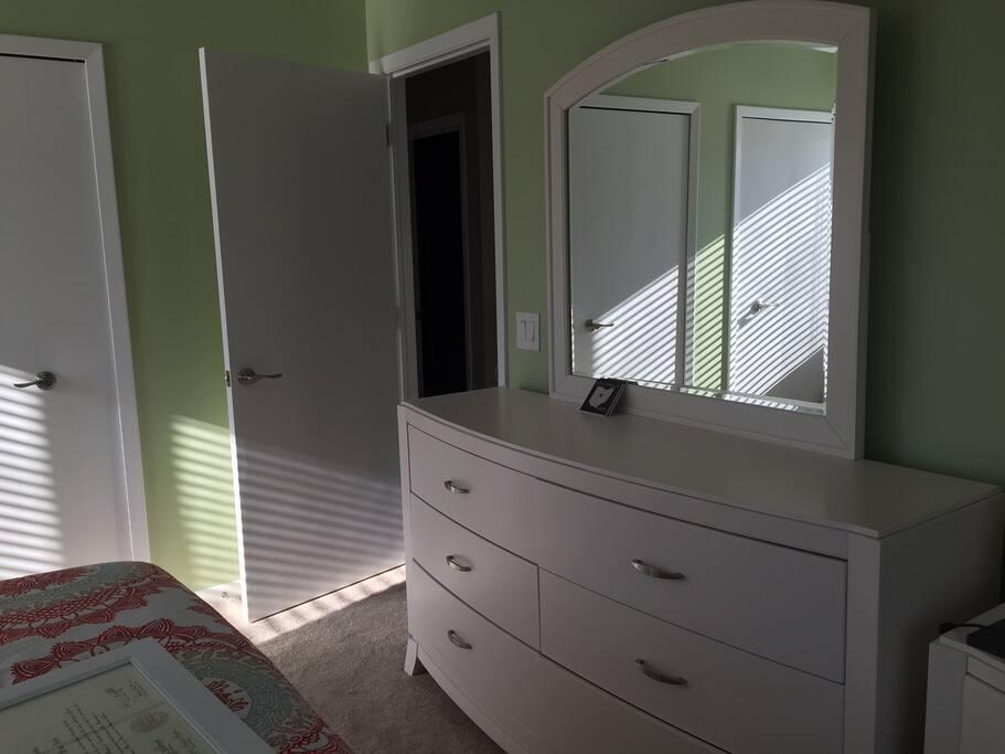 Bedroom 1 - dresser, desk, nightstand, closet, mounted TV.