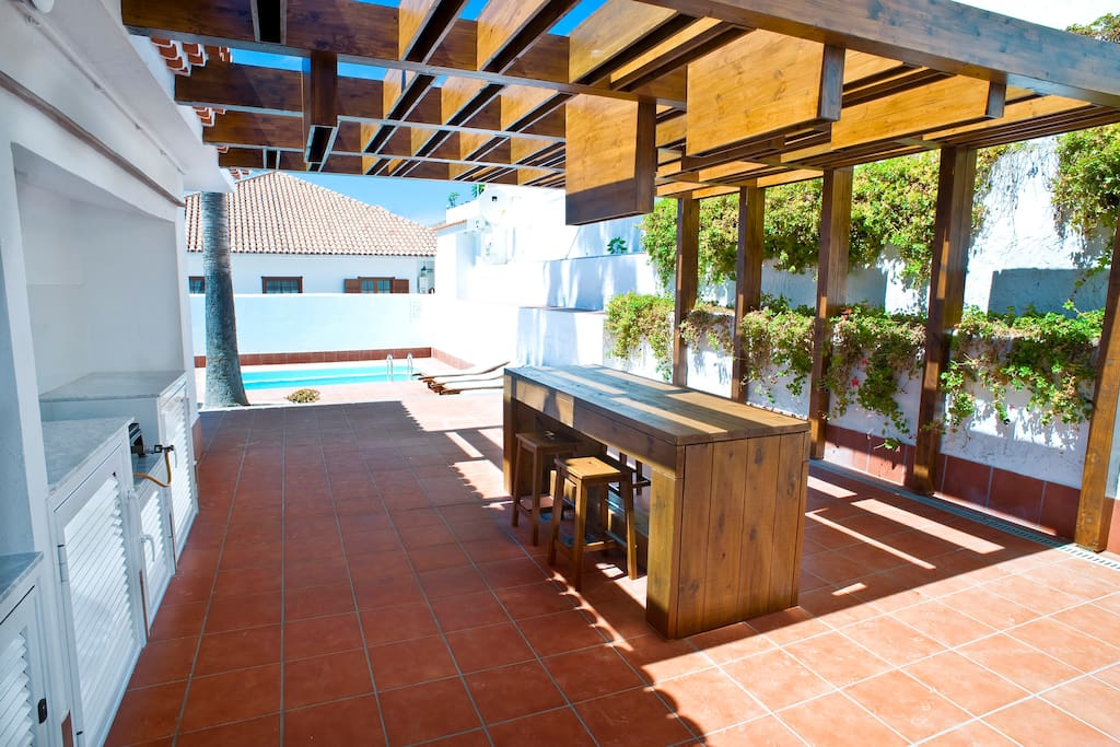 Outdoor kitchen & dining area with swimming pool