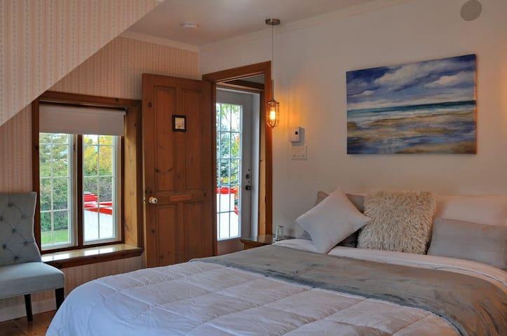 Chambre sur la montagne équipée d'un lit queen.  Portes patio, balcon privé sur la montagne,  entrée privée du gîte