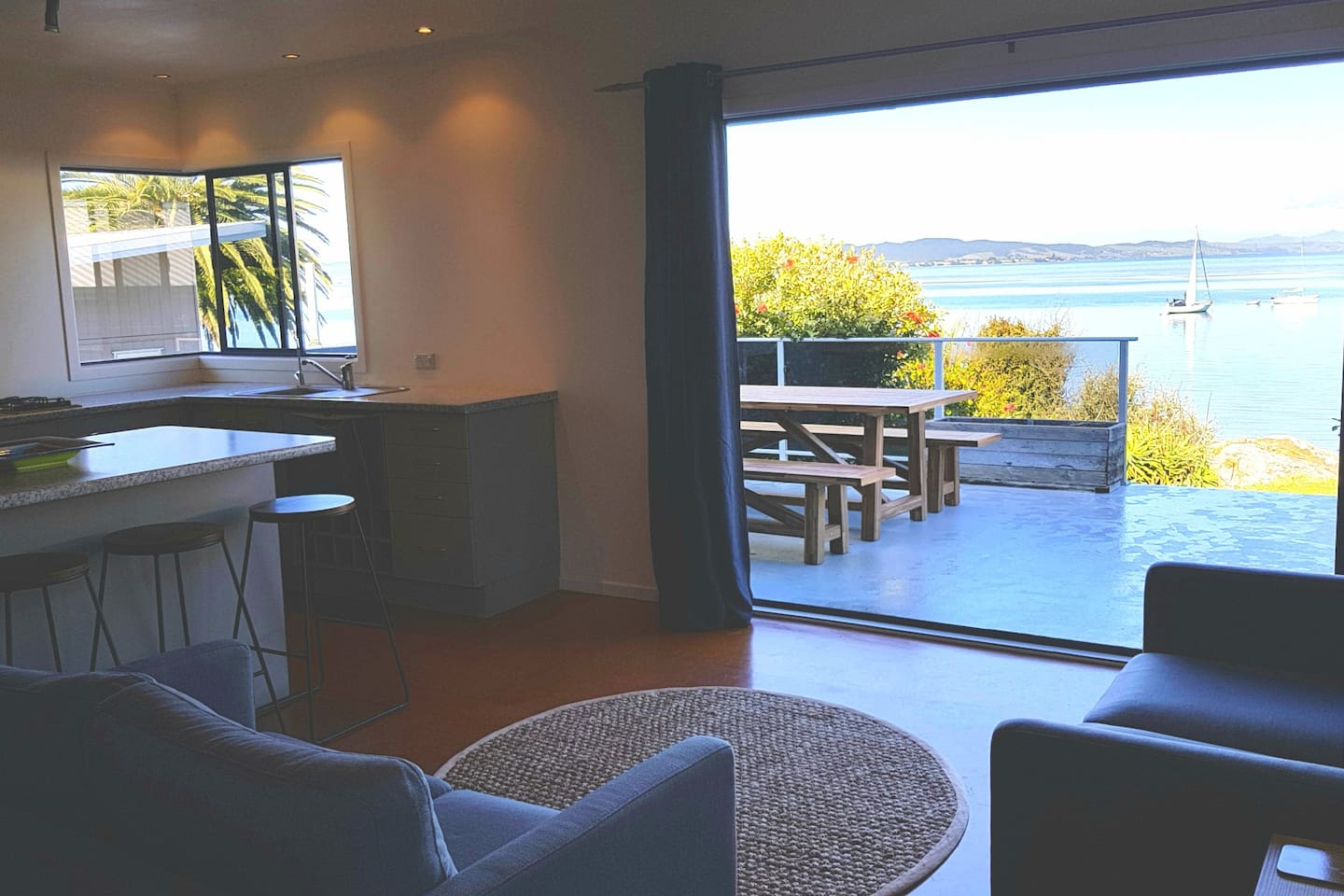 The living area opens onto the deck by a large bifold door. Look at that view!
